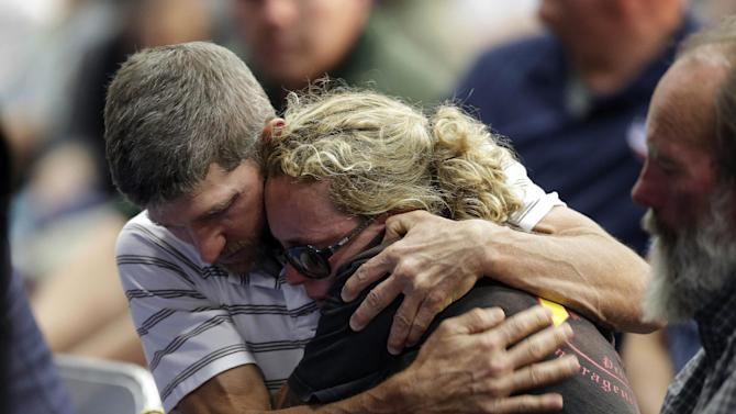 A couple embraces during a memorial service Monday, July 1, 2013, in Prescott, Ariz., honoring the 19 firefighters killed battling a wildfire near Yarnell, Ariz., Sunday. The elite crew of firefighters was overtaken by the out-of-control blaze as they tried to protect themselves from the flames under fire-resistant shields. (AP Photo/Chris Carlson)