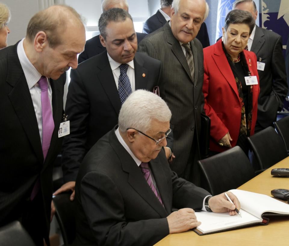 Palestinian President Mahmoud Abbas, bottom, signs a book while surrounded by his advisors before a meeting with United Nations Secretary-General Ban Ki-moon during the 66th session of the General Assembly at United Nations headquarters, Monday, Sept. 19, 2011.  (AP Photo/Seth Wenig)