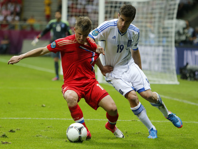 Greece's Sokratis Papastathopoulos pulls Russia's Andrei Arshavin's jersey during the Euro 2012 soccer championship Group A  match between Greece and Russia in Warsaw, Poland, Saturday, June 16, 2012.