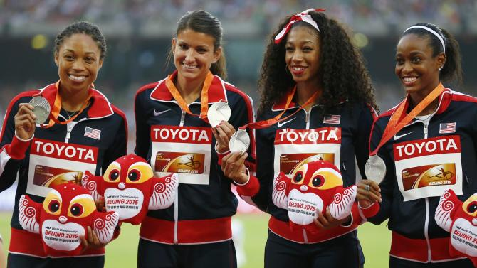 Allyson Felix of the US and teammates Prandini, Todd and Gardener, silver medallists, pose on the podium after the women's 4 x 100 metres relay event during the 15th IAAF World Championships at the National Stadium in Beijing