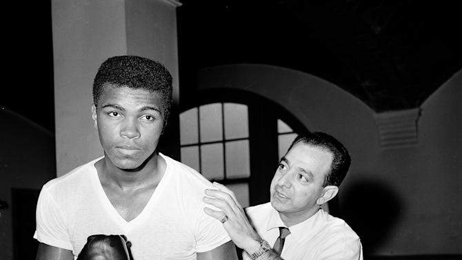 FILE - In this Feb. 8, 1962 file photo, a young Muhammad Ali  is seen with his trainer Angelo Dundee at City Parks Gym in New York. The three-time heavyweight boxing champion will celebrate a milestone birthday Tuesday, Jan. 17, 2012,  when he turns 70. Ali will be surrounded by friends who are gathering Saturday evening, Jan. 14,  for a birthday party at the Muhammad Ali Center in his hometown of Louisville. (AP Photo/Dan Grossi, File)