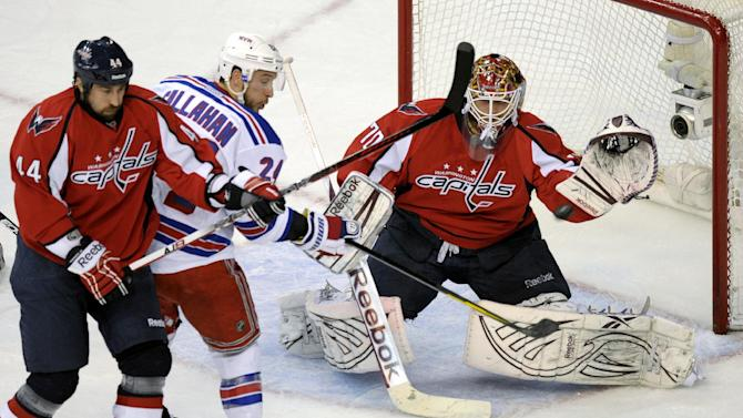 Washington Capitals goalie Braden Holtby (70) prepares to catch the puck as Capitals defenseman Roman Hamrlik (44) and New York Rangers right wing Ryan Callahan (24) battle in the first period of Game 6 of a second-round NHL hockey Stanley Cup playoff series, Wednesday, May 9, 2012, in Washington. (AP Photo/Susan Walsh)