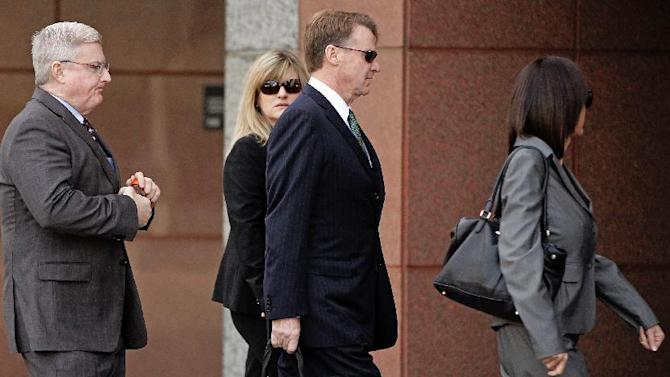 Former Deutsche Bank executive Brian Mulligan, center, arrives with his wife Victoria, second from left, with unidentified attorneys, at the Edward R. Roybal Federal Building, Tuesday, Jan. 21, 2014, in Los Angeles. A trial began for Mulligan, who sued the city of Los Angeles and two police officers claiming they beat him during a bizarre incident in May 2012. He is seeking $20 million in damages in a lawsuit filed in federal court. Officers said Mulligan told them he had ingested a type of bath salts known as White Lightning. Mulligan, who has no prior criminal record, once served as co-chairman of Universal Studios and chief financial officer of Seagram Co. (AP Photo/Damian Dovarganes)