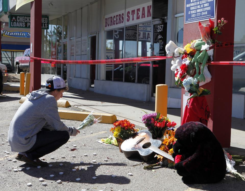 A young man leaves flowers at an informal memorial at Fero's Bar and Grill in Denver on Thursday, Oct. 18, 2012. The bodies of a man and four woman were discovered after firefighters extinguished a fire at the bar early Wednesday morning. Police have arrested three suspects in the case. (AP Photo/Ed Andrieski)