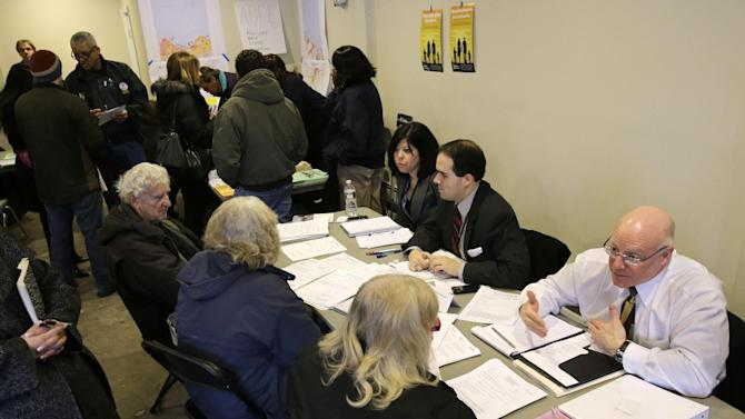 """New Jersey Department of  Banking and Insurance employee, Christian Traum, right, and workers from the Federal Emergency Management Agency and state agencies help residents at a center in Union Beach, N.J., Tuesday, Feb. 5, 2013. New Jersey Gov. Chris Christie said the National Flood Insurance Program's handling of claims in New Jersey has been """"a disgrace,"""" complaining that the program has been far too slow to resolve claims from Superstorm Sandy, with 70 percent of cases unresolved three months after the disaster. (AP Photo/Mel Evans)"""