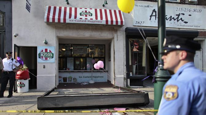 Investigators look over the debris of a fallen security door outside a Rita's Water Ice store in the Brewerytown section of Philadelphia on Saturday, June 28, 2014. Investigators tell Philly.com that the metal security door detached and fell on a 3-year-old girl who died. (AP Photo/Joseph Kaczmarek)