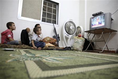 A Free Syrian Army fighter watches U.S. President Obama's speech with his family in Damascus