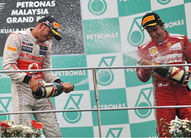 Winner Ferrari driver Fernando Alonso of Spain (R), Sauber-Ferrari driver Sergio Perez (L) of Mexico and McLaren-Mercedes driver Lewis Hamilton (C) of Britain celebrate on the podium with champagne af