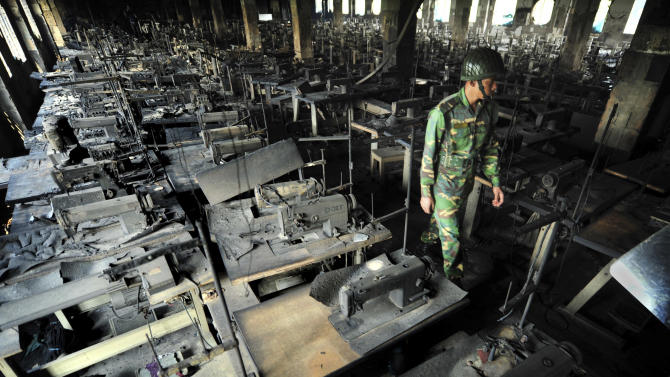 A Bangladeshi police officer walks between rows of burnt sewing machines in a garment factory outside Dhaka, Bangladesh, Sunday, Nov. 25, 2012. At least 112 people were killed in a late Saturday night fire that raced through the multi-story garment factory just outside of Bangladesh's capital, an official said Sunday. (AP Photo/ khurshed Rinku)