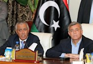 Ali Zeidan (left) and head of the General National Congress Nouri Bousahmein give a press conference at government headquarters in Tripoli on October 10, 2013 shortly after Zeidan's release
