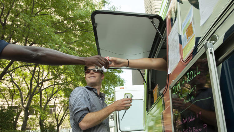 In this July 12, 2012 photo, a customer is seen purchasing a drink from the Duck N Roll food truck in downtown Chicago. A proposed ordinance would finally allow food trucks to cook and prepare food but continue to ban them from setting up shop any closer than 200 feet away from restaurants and capping the time they can stay put in one spot at two hours. The full City Council could vote on the proposal as soon as next week. (AP Photo/Sitthixay Ditthavong)