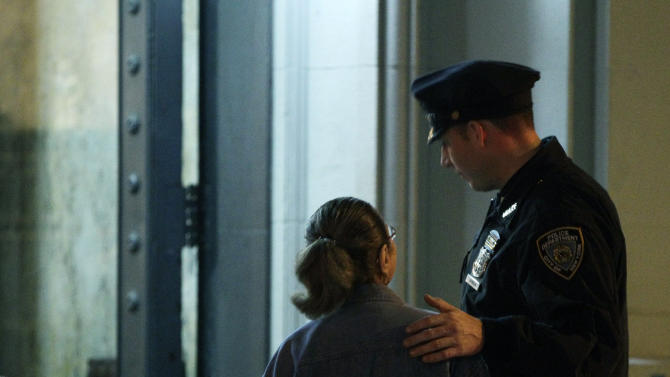 A New York City police officer comforts a woman in front of the luxury Manhattan apartment building where police say a nanny stabbed two small children to death in a bathtub and then stabbed herself in New York, Thursday, Oct. 25, 2012. Police say the children's mother found the scene after returning home with another child. (AP Photo/Kathy Willens)