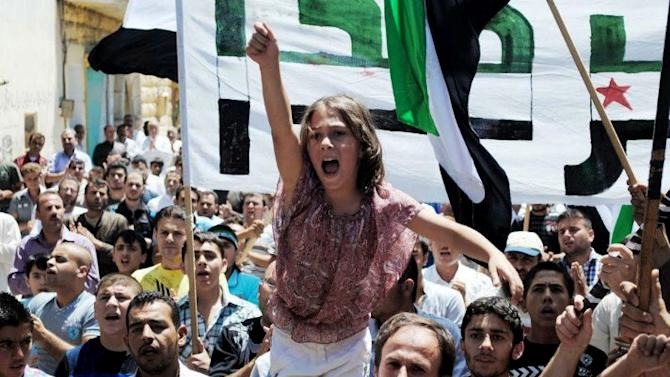 In this citizen journalism image provided by the Local Coordination Committees in Syria and accessed on Friday, June 29, 2012, a Syrian girl chants slogans during a demonstration in Idlib, north Syria. Syria's main opposition group said nearly 800 people have been killed in violence across the country in the past week which saw some of the bloodiest violence in the 16-month uprising against President Bashar Assad. (AP Photo/Local Coordination Committees in Syria) THE ASSOCIATED PRESS IS UNABLE TO INDEPENDENTLY VERIFY THE AUTHENTICITY, CONTENT, LOCATION OR DATE OF THIS HANDOUT PHOTO