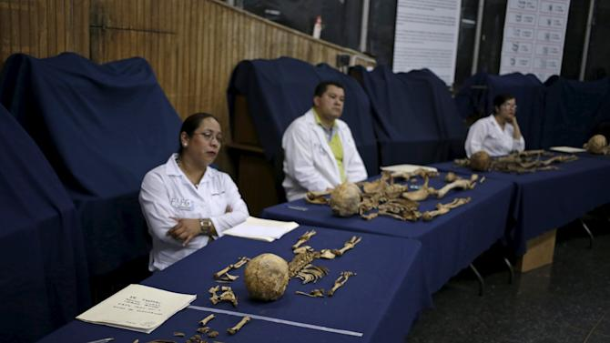 Anthropolgists sit before victims of the domestic armed conflict in Guatemala, during a program to identify dead immigrants in Mexico and U.S., in Guatemala City