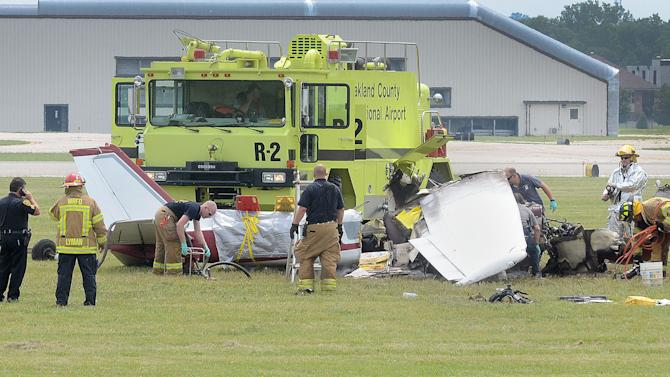 Emergency personnel looks over the scene of a plane crash at Oakland International Airport in Waterford, Mich., Friday, June 21, 2013. A pilot and three passengers have were killed after a small plane crashed shortly after takeoff from the airport northwest of Detroit. Airport spokesman Dave VanderVeen says the Cessna 172 went down about 1:40 p.m. Three people on board were killed instantly, while the fourth died later at a hospital. (AP Photo/The Oakland Press, Vaughn Gurganian)
