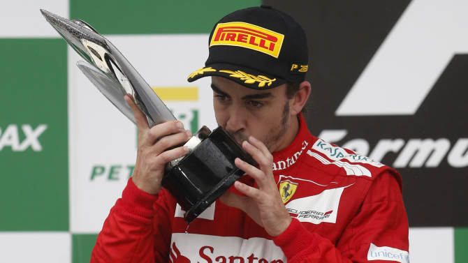 Ferrari driver Fernando Alonso, of Spain, kisses his second place trophy at the podium of the Formula One Brazilian Grand Prix at Interlagos race track in Sao Paulo, Brazil, Sunday, Nov. 25, 2012. Red Bull driver Sebastian Vettel, of Germany, overcame a first-lap crash to clinch his third straight Formula One championship title on Sunday, finishing sixth in an incident-filled Brazilian Grand Prix won by Jenson Button under pouring rain. (AP Photo/Victor R. Caivano)