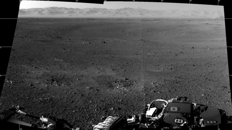 This image released on Wednesday Aug. 8, 2012 by NASA, shows a mosaic of the first two full-resolution images of the Martian surface from the Navigation cameras on NASA's Curiosity rover. The rim of Gale Crater can be seen in the distance beyond the pebbly ground.   The foreground shows two distinct zones of excavation likely carved out by blasts from the rover's descent stage thrusters. (AP Photo/NASA)