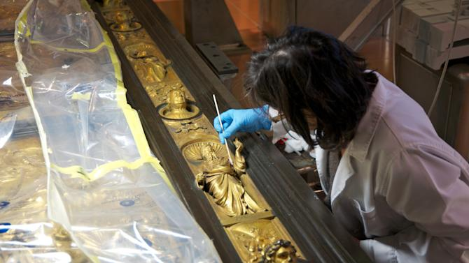"""In this undated photo provided by the Opera di Santa Maria del Fiore, a woman restores the original panel of the """"Door of Paradise"""" in Florence, Italy. The original gilded bronze door, so splendid it was dubbed the """"Door of Paradise"""" by Michelangelo, will be seen again in Florence after 27 years of restoration to remove damage by pollution, vandalism and the wear and tear of centuries. But Lorenzo Ghiberti's 15th-century door won't be going back in its place on the baptistry of Florence's duomo, or cathedral. Starting in September, it will go on display in a Florence museum, Museo dell'Opera di Santa Maria del Fiore, to preserve it from renewed damage. (AP Photo/Nicolò Orsi Battaglini, Opera di Santa Maria del Fiore)"""