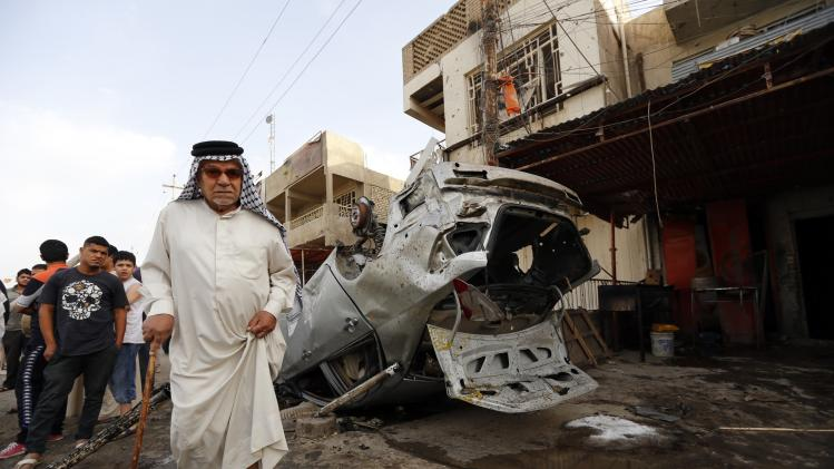 Man walks past the site of a car bomb attack in Baghdad's Habibiya district