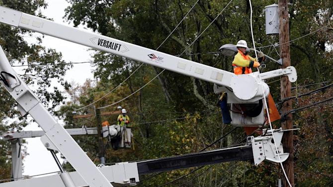 FILE - This  photo taken Oct. 30, 2012, shows a utility crew working on damaged power lines in the aftermath of superstorm Sandy in Berlin, Md. One week before a close election, superstorm Sandy has confounded the presidential race, halting early voting in many areas, forcing both candidates to suspend campaigning and leading many to ponder whether the election might be postponed. It could take days to restore electricity to all of the more than 8 million homes and businesses that lost power when the storm pummeled the East Coast. That means it's possible that power could still be out in some states on Election Day _ a major problem for areas that rely on electronic voting machines.  (AP Photo/Alex Brandon)