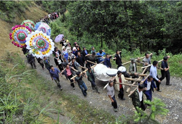 "Villagers carry a dead bull known as ""King of Bulls"", towards its tomb during its funeral in Leishan county, Guizhou province"