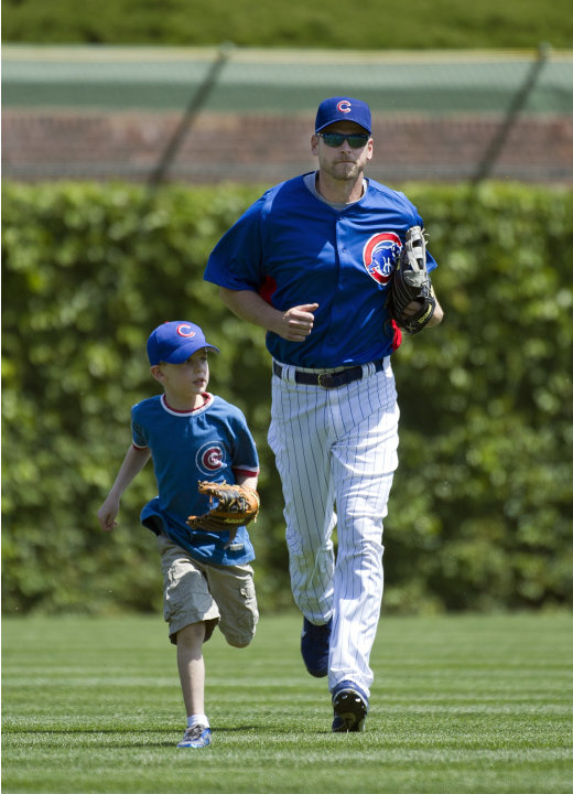 Chicago Cubs relief pitcher Kerry Wood, right, runs in from the outfield with his son Justin during batting practice before a baseball game against the Chicago White Sox, Friday, May 18, 2012, in Chic