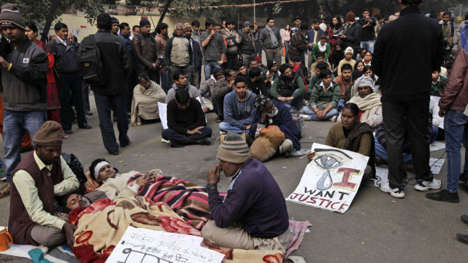 """Indian men lie on a street while on a hunger strike during a protest in New Delhi, India, Monday, Dec. 31, 2012. A young woman who died after being gang-raped and beaten on a bus in India's capital was cremated privately as millions of grieving, angry residents demanded greater protection for women from sexual violence. A placard in front reads as, """"Against women harassment, 8th day of Hunger Strike.""""  (AP Photo/Manish Swarup)"""