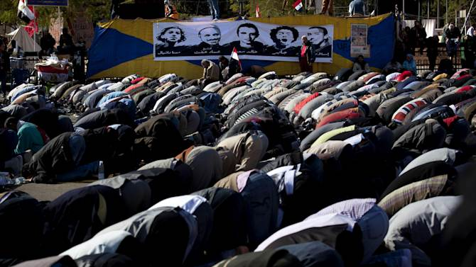 "Egyptian protesters opposing president Mohammed Morsi attend Friday prayers beneath with a poster depicting protesters killed in the Egyptian revolution, at Tahrir Square, Cairo, Egypt, Friday, Dec. 7, 2012. Arabic on the poster reads their names from right ""Islam, Jaber, Khalid Said, Emad Effat and Mina Daniel."" Thousands of Egyptians took to the streets after Friday midday prayers in rival rallies and marches across Cairo, as the standoff deepened over what opponents call the Islamist president's power grab, raising the specter of more violence. (AP Photo/Nasser Nasser)"