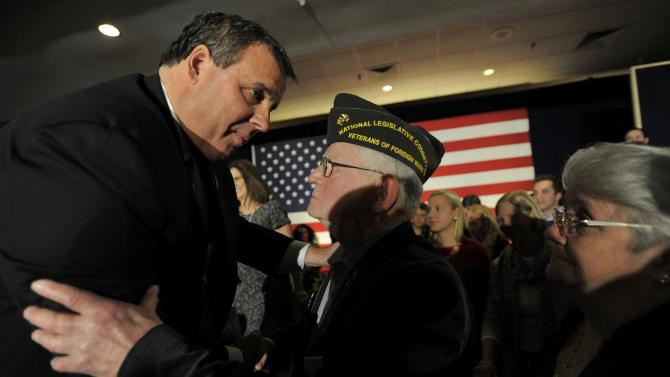 U.S. Republican presidential candidate and New Jersey Governor Christie shakes hands with retired marine Sergent major Chevalier after addressing the crowd at his primary election night party Nashua