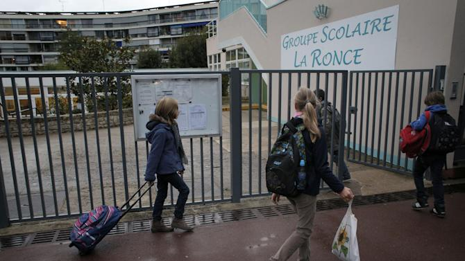 Students enter the school of La Ronce in Ville d'Avray, west of Paris, Friday, Oct. 5, 2012. French children go to school four days a week with about two hours each day for lunch. And they have more vacation than their counterparts almost anywhere in the West. As a candidate, President Francois Hollande promised to change things by adding a fifth day of classes on Wednesday while shortening the school day and education minister, Vincent Peillon, will decide this month how to carry out the reform. (AP Photo/Christophe Ena)