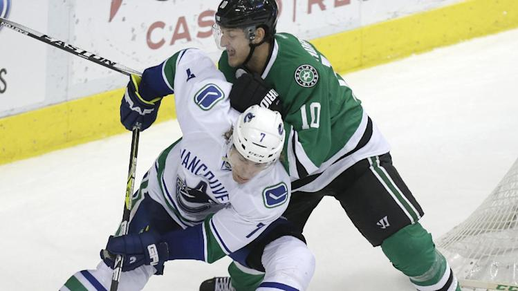 Vancouver Canucks left wing David Booth (7) and Dallas Stars center Shawn Horcoff (10) skate for the puck during the second period of an NHL hockey game Thursday, March 6, 2014, in Dallas. (AP Photo/LM Otero)