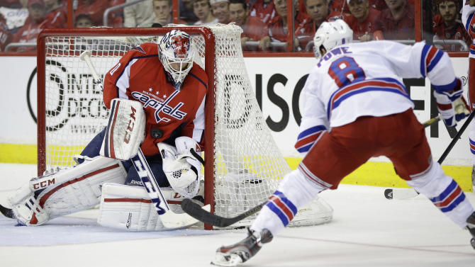 Washington Capitals goalie Braden Holtby, left, makes a save against New York Rangers right wing Darroll Powe during the second period in Game 2 of an NHL hockey Stanley Cup first-round playoff series, Saturday, May 4, 2013, in Washington. (AP Photo/Evan Vucci)