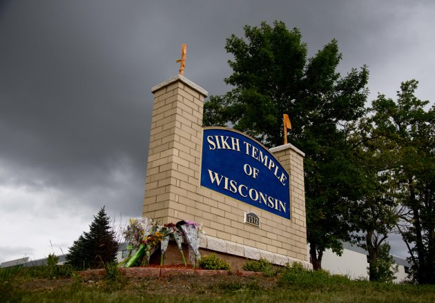 Flowers lie on the sign to the Sikh temple of Wisconsin where members were allowed to re-enter for the first time in Oak Creek, Wis., Thursday, Aug 9, 2012. The mass shooting last Sunday claimed six members of the temple.
