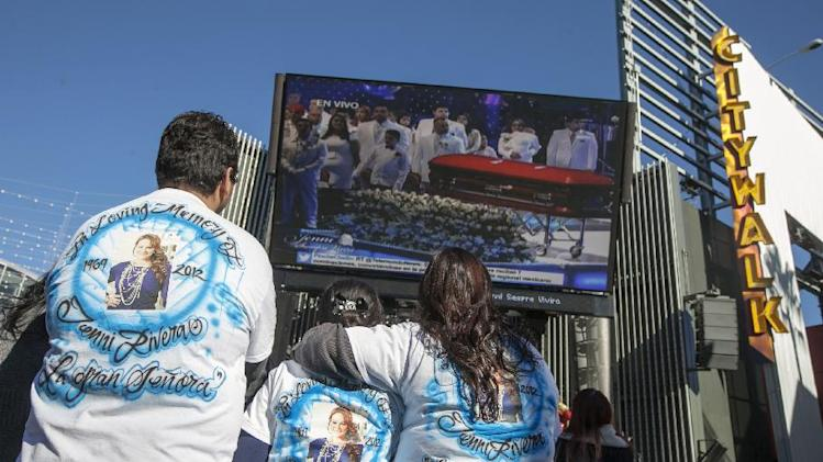 Fans mourn Jenni Rivera at a memorial televised a on giant television in Universal City in Los Angeles Wednesday, Dec. 19, 2012. The 43-year-old Rivera and six others died Dec. 9 in a crash that remained under investigation. Rivera sold more than 15 million copies of her 12 major-label albums. Her soulful singing style and honesty about her tumultuous personal life won her fans on both sides of the U.S.-Mexico border. She was also an actress and reality-TV star.  (AP Photo/Damian Dovarganes)