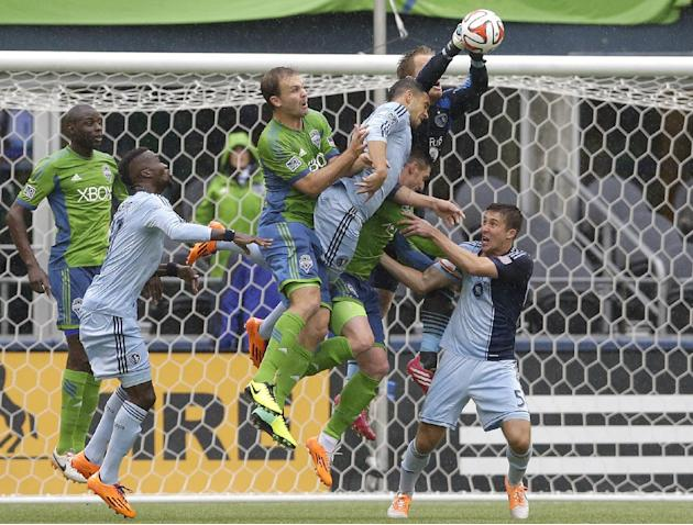 Sporting Kansas City goalkeeper Eric Kronberg, upper right, leaps to make a stop as he tangles with Seattle Sounders' Chad Marshall, third from left, and Kenny Cooper, second from lower right, alo
