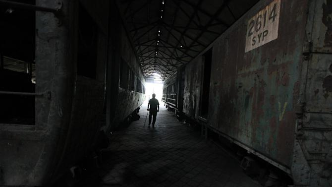 Historian John Godwin walks between two abandoned train cars in Lagos, Nigeria, on Saturday, April 13, 2013. The Nigerian Railway Corp., while recently restarting service from Lagos to the northern city of Kano, still has relics from the past littering the grounds of its headquarters in Lagos. Historians hope to preserve some of these old locomotives and train cars for future generations to see. (AP Photo/Jon Gambrell)