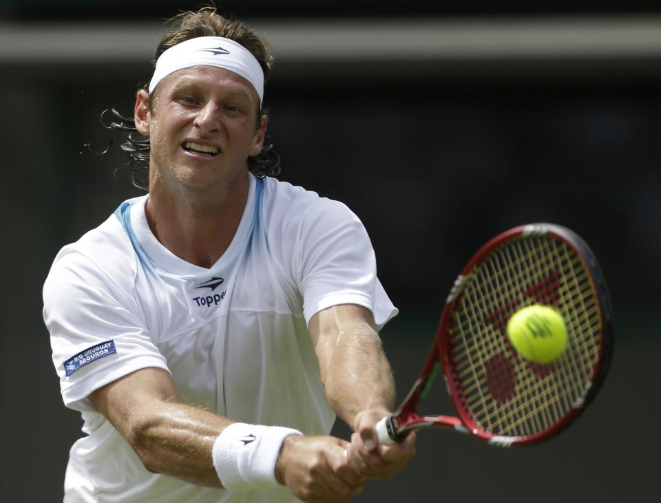 David Nalbandian of Argentina plays a return to Janko Tipsarevic of Serbia during a first round men's singles match at the All England Lawn Tennis Championships at Wimbledon, England, Monday, June 25, 2012. (AP Photo/Tim Hales)