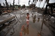 A child stands in a street lined with destroyed buildings following days of sectarian violence in Sittwe, capital of Myanmar&#39;s western state of Rakhine in June 2012. UN leader Ban Ki-moon warned Saturday that Muslim-Buddhist unrest in Myanmar&#39;s Rakhine state could hit the country&#39;s landmark reforms and spill across borders, a UN spokesman said