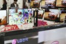 Customers look at LG Electronics' TV sets at a store in Seoul