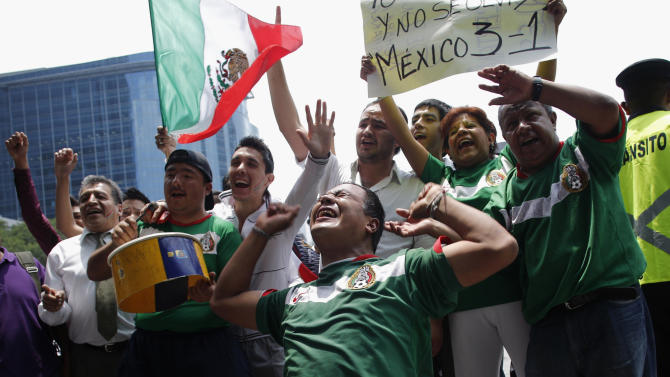 People celebrate Mexico winning against Japan after their men's semi-final soccer match at London 2012 Olympic Games in downtown Mexico City