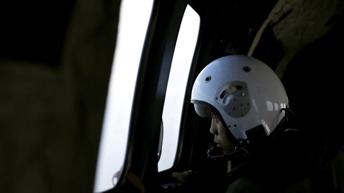 File photo of an Indonesian Air Force soldier looking through the window during a search operation for passengers onboard AirAsia Flight QZ8501 off the Java sea