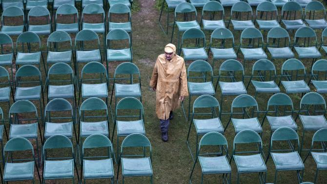 An Indian security personnel stands guard amid empty chairs installed at the venue of the Republic Day parade in New Delhi