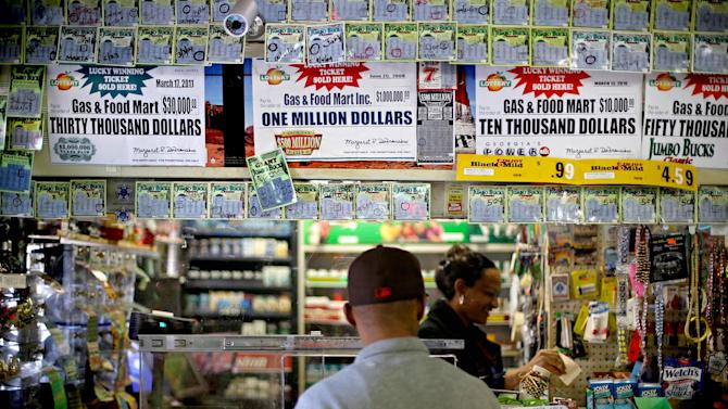 A customer waits for his lottery ticket to print out at a convenience store, Monday, Nov. 26, 2012, in Atlanta. As the Powerball jackpot soars, a Georgia Lottery official says the agency is working to get its equipment operational again after some machines have been down. Georgia Lottery spokeswoman Kimberly Starks confirmed that some machines were not working properly. She said Monday afternoon that lottery officials are aware of the situation, and are working to correct the problems. (AP Photo/David Goldman)
