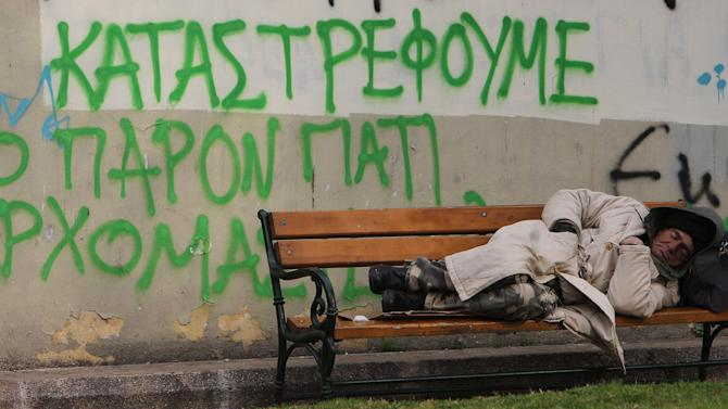 A homeless man sleeps on a bench outside the municipal culture center of Athens as graffiti reads ''We destroy the present GAP-George Papandreou (former Greek Prime Minister) we are coming,'' as temperatures fell below zero degrees Celsius (32 Fahrenheit)  around the country, Tuesday, Jan. 31, 2012. The country's national debt exceeded euro350 billion last year, and without the bond-swap deal would not be considered sustainable as Greek gross domestic product is set to slow to euro215 billion in 2012, in a fourth year of recession, according to state budget figures. (AP Photo/Thanassis Stavrakis)