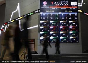 Indonesian traders walk in front of an Indonesia Stock Exchange board in Jakarta