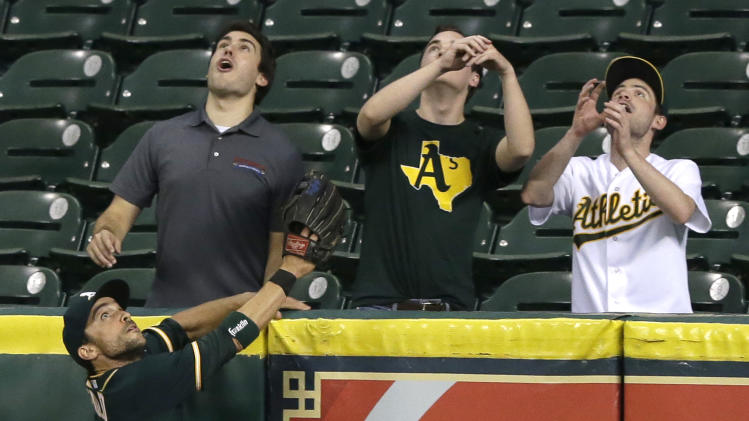 Oakland Athletics center fielder Sam Fuld (23) and fans watch a solo home run by Houston Astros' Chris Carter go over their heads in the ninth inning of a baseball game Wednesday, Aug. 27, 2014, in Houston. Oakland won 5-4. (AP Photo/Pat Sullivan)
