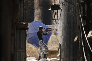 A Free Syrian Army fighter aims his weapon as he takes…