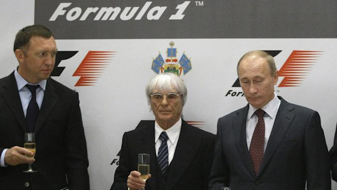 FILE - In this Thursday, Oct. 14, 2010 file photo, then, Russian Prime Minister Vladimir Putin, second right, Formula One chief Bernie Ecclestone, second left, and Oleg Deripaska, toast after a signing ceremony in the Black Sea resort of Sochi, southern Russia. Oleg Deripaska's Basic Element, insists its projects were all designed to be profitable. The company is building an Olympic village and a seaport and has just finished revamping the Sochi airport, for a combined cost of $1.4 billion. (AP Photo/Mikhail Metzel, File)