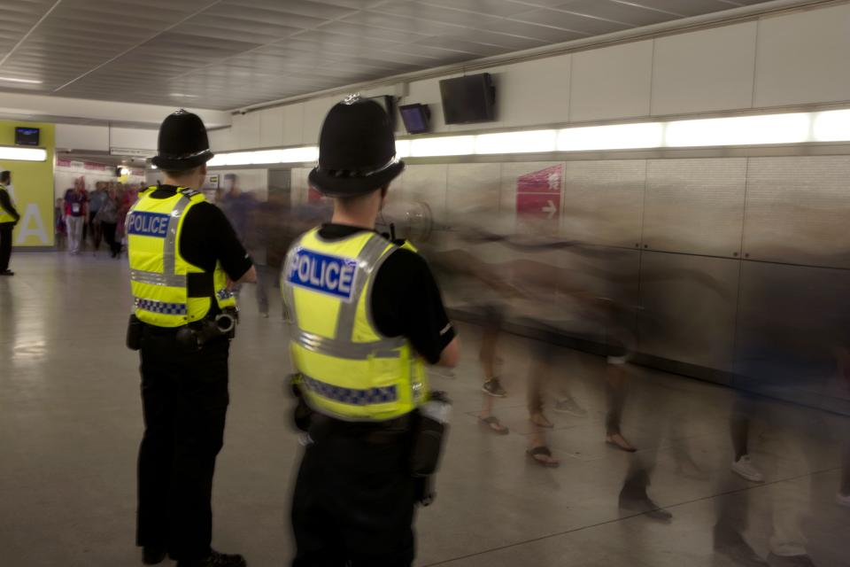 Police officers stand guard as people arrive at the Olympic Park at the 2012 Summer Olympics, Sunday, July 29, 2012, in London. (AP Photo/Emilio Morenatti)
