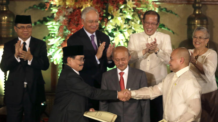 Government peace negotiator Marvic Leonen, right, and Moro Islamic Liberation Front chief negotiator Mohagher Iqbal, left, shake hands as they exchange signed peace documents following formal signing ceremony Monday Oct. 15, 2012 at Malacanang Palace in Manila, Philippines. Witnessing the signing are Malaysian peace broker Dato Tengko Abdul Ghafar, center, and from left second row, MILF Chair Al Haj Murad, Malaysian Prime Minister Najib Razak, Philippine President Benigno Aquino III, and Government peace negotiator Teresita Deles. Muslim rebels and the Philippine government overcame decades of bitter hostilities and took their first tentative step toward ending one of Asia's longest-running insurgencies with the ceremonial signing of a preliminary peace pact Monday that both sides said presented both a hope and a challenge. (AP Photo/Bullit Marquez)